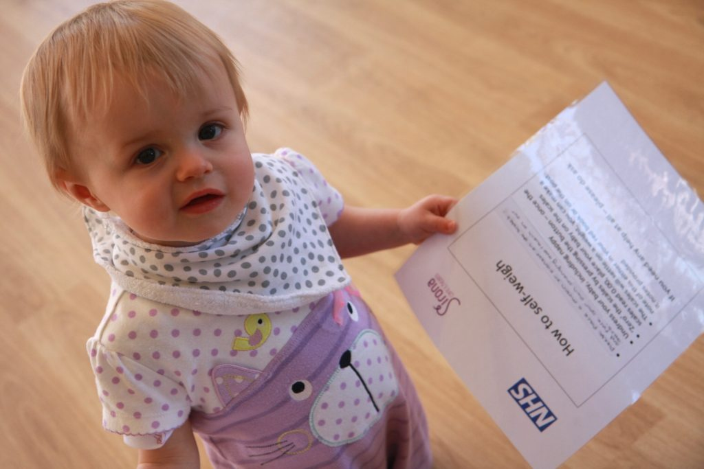 A baby holding a piece of paper looks at the camera during a baby hub session organised by the health visitors