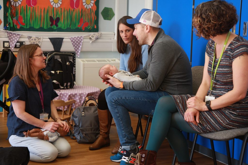 A health visitors holding a doll chats to two new parents, who are holding a small baby. Another health visitor looks on.