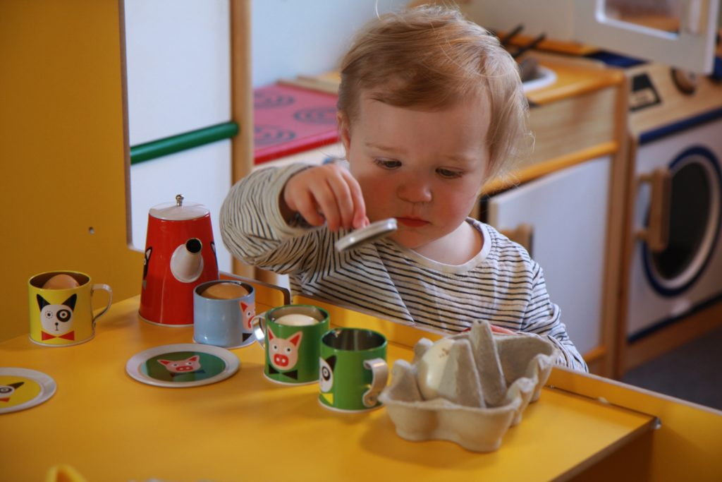 A toddler plays with a tea set and an egg box at a baby hub session